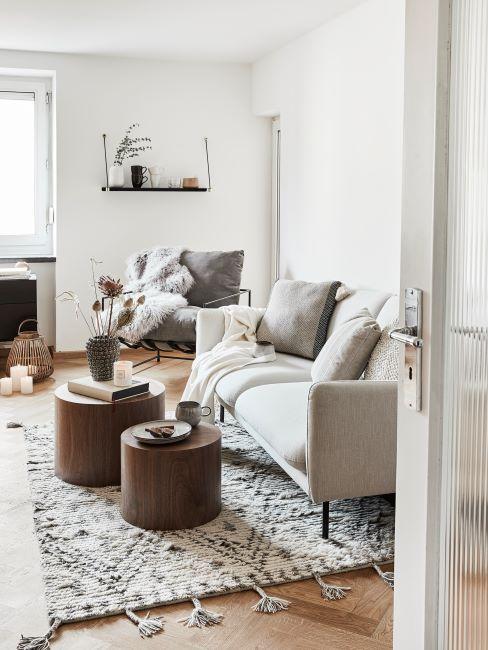 salon scandinave, canappé blanc cassé ou beige clair, ensemble de tables basses rondes en bois, fauteuil moderne et rembourré, décoré d'un plaid cosy
