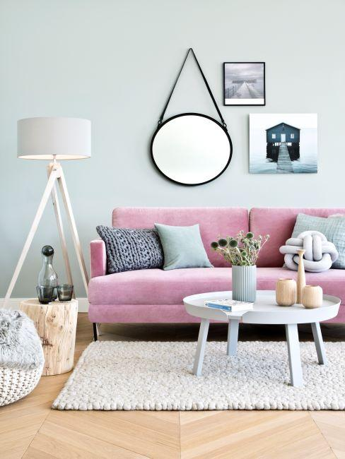 canapé rose velours, miroir mural rond avec sangle de suspension, lampadaire scandinave, table basse blanche décorée des vases et bougies, tapis épais blanc, salon girly, couleurs pastel