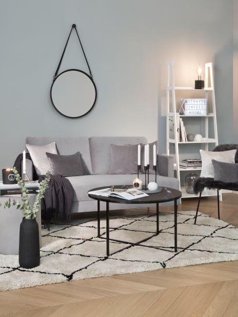 canapé gris, mur de salon gris, miroir mural rond, tapis longs poils crème, étagère style échelle, salon moderne, table basse métal noir décorée d'un chandelier