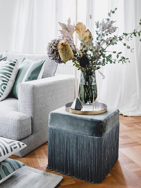 Pouf en velours gris foncé comme table d'appoint avec vase et fleurs séchées