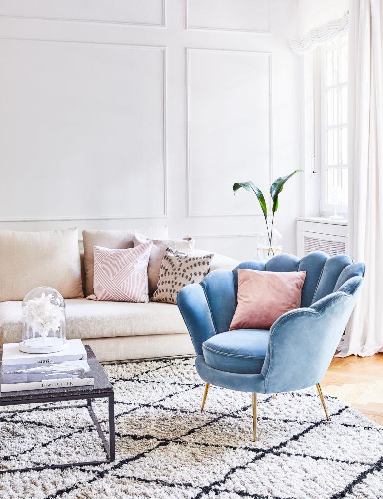 salon avec fauteuil en velours bleu, tapis berbère et canapé beige
