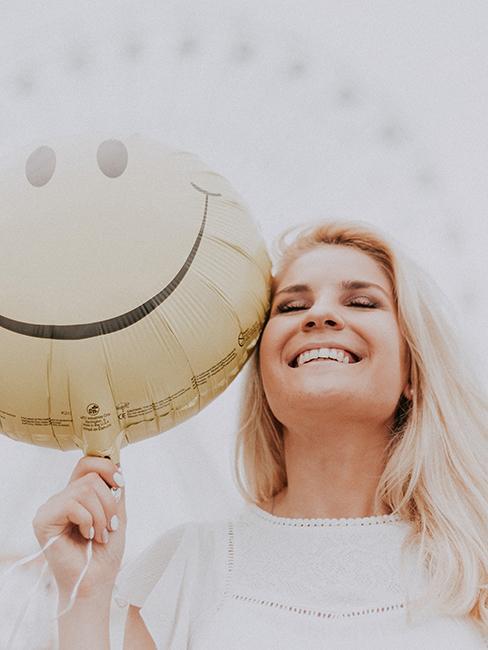Femme entrain de sourire en tenant un ballon smiley à la main