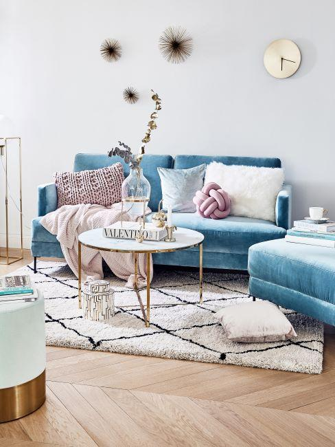 canapé velours bleu clair, table basse ronde, coussins et plaid pastel, tapis poils longs
