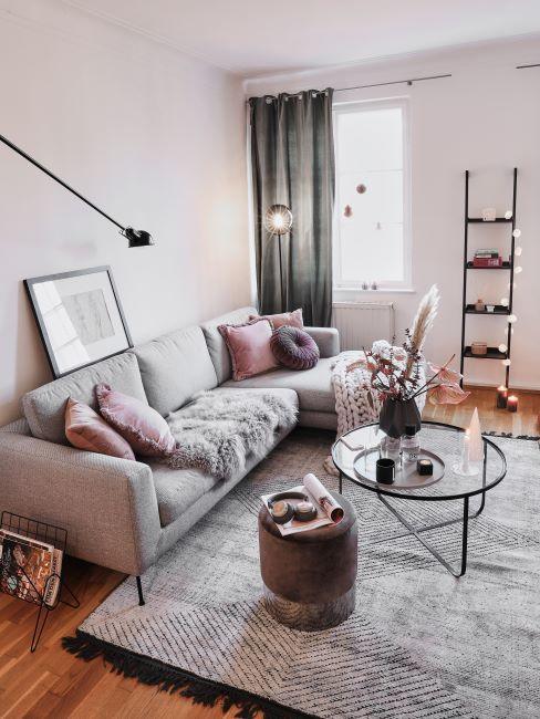 canapé tissu gris, coussins roses, échelle décorative, bougies, tapis gris shaggy, table basse ronde en verre, rideaux gris