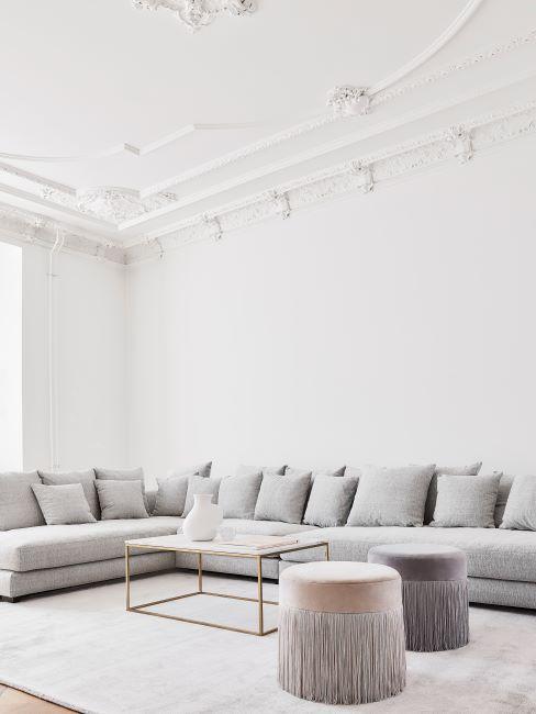 grand canapé d'angle tissu gris coussins, plafond très haut, moulures sur le plafond, minimalisme
