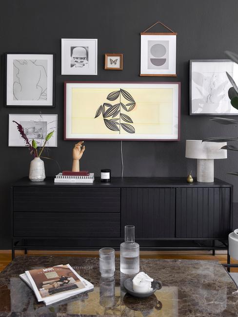 Salon avec mur noir, mur de cadres et commode noire