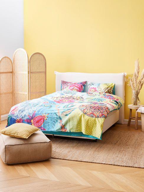 linge de lit multicolore, chambre à coucher murs jaunes, pouf, tapis, paravan en matière naturelle