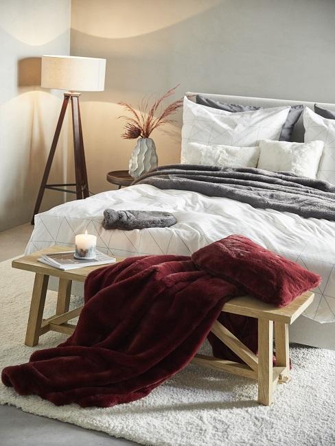 chambre à couche, bout de lit en bois, plaid rouge foncé, lampadaire trépied, linge de lit, parful ambiance