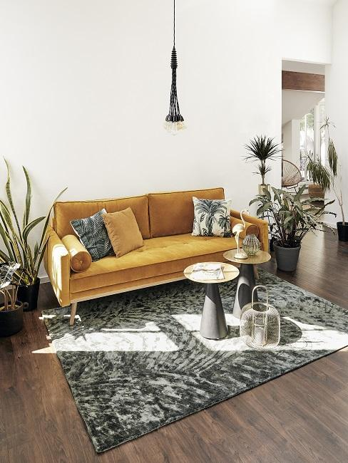 salon ethno avec canapé en velours jaune moutarde, grand tapis et plantes vertes