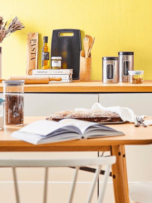 Cuisine avec mur jaune, table en vois avec un livre ouvert posé dessus