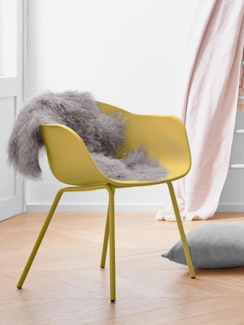 chaise jaune avec accoudoirs et fausse peau de bête grise