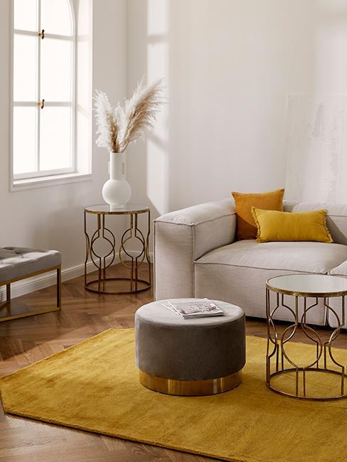 Salon avec canapé gris, pouf gris, coussins jaunes et fleurs de pampa