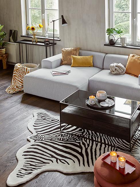 Salon avec canapé gris, coussins jaunes, table basse en bois et tapis zebre