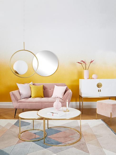 Salon avec mur jaune et blanc, canapé rose, tapis bleu et rose pastel