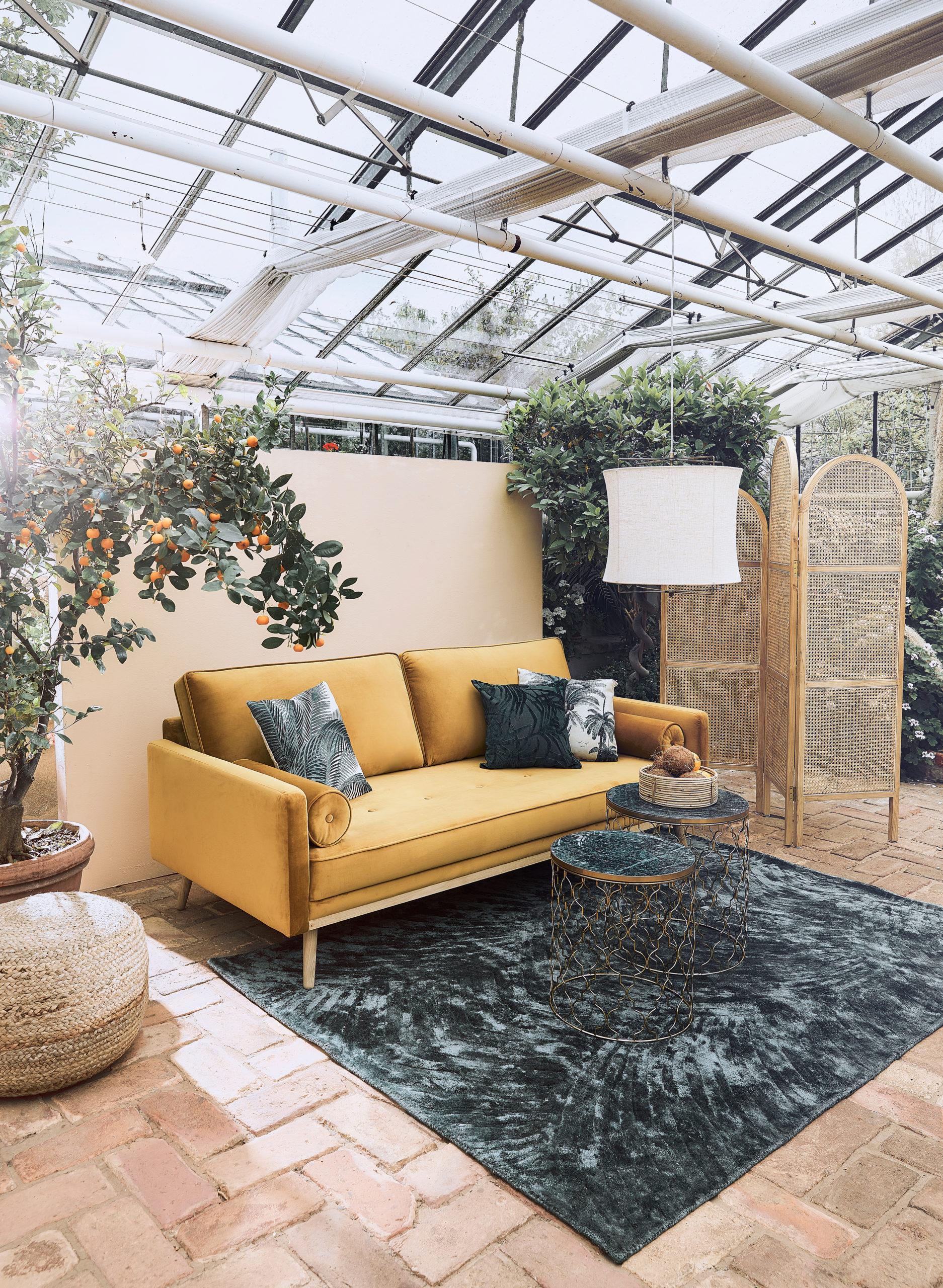 Veranda avec canapé jaune, tapis gris vert et coussins tropicaux