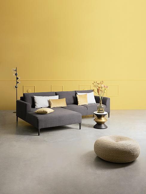Salon avec canapé gris, mur jaune et pouf en jute