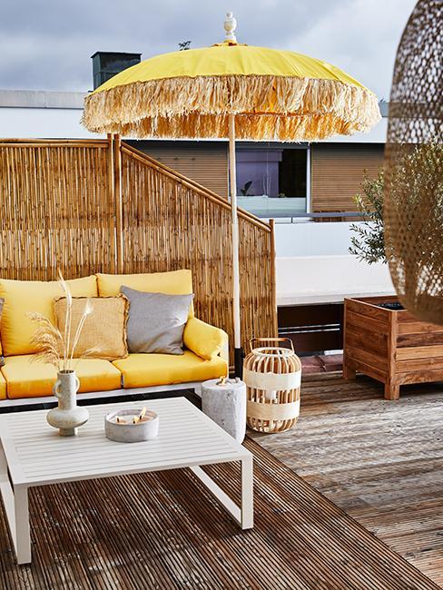 Terrasse avec canapé de jardi jaune, parasol jaune et table blanche