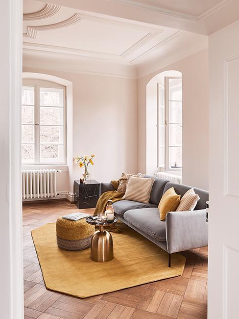 Salon avec canapé gris, tapis jaune, coussins jaune et pouf