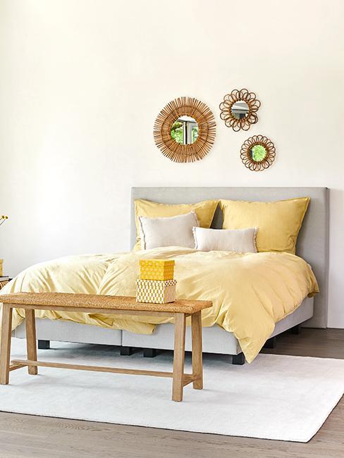 Chambre avec cadre de lit gris, coussin et hausse de couette jaune et banc en bois