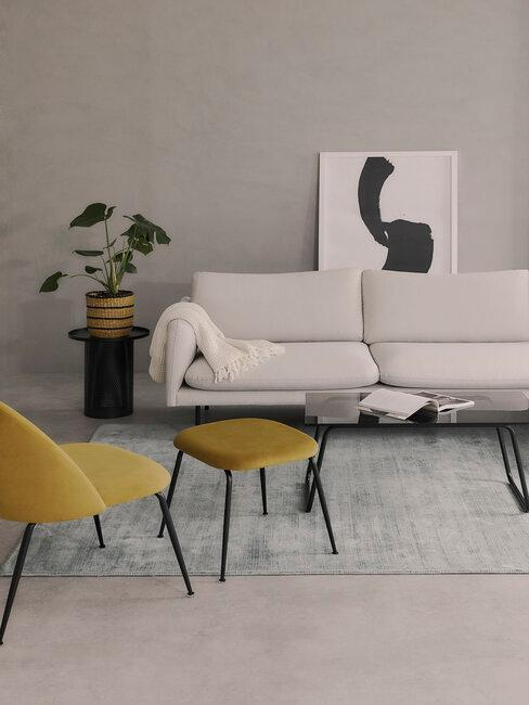 Salon avec fauteuil et repose pied aune, canapé beige et mur gris