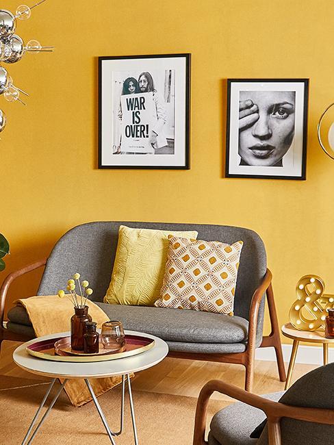 salon avec mur jaune, canapé gris, et affiches rétro