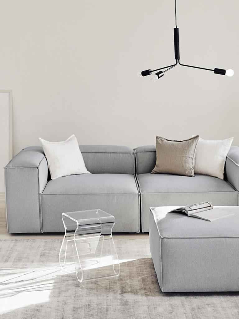 Canapé gris avec tabouret transparent et coussins blancs