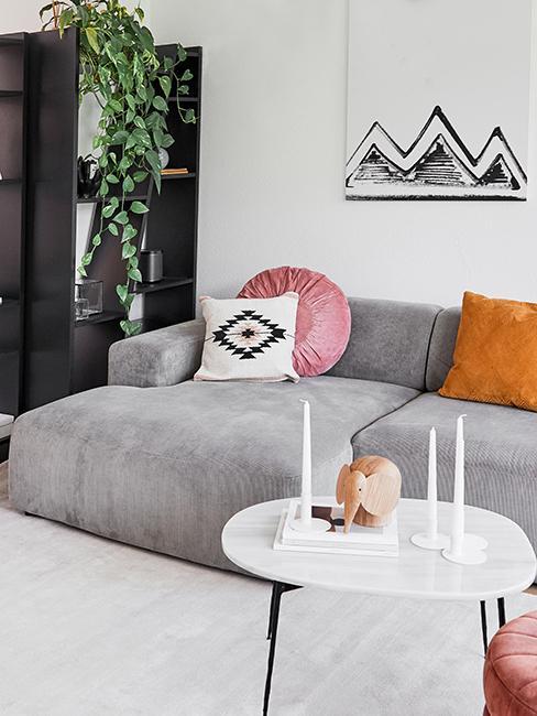 canapé gris avec coussins colorés et table basse blanche