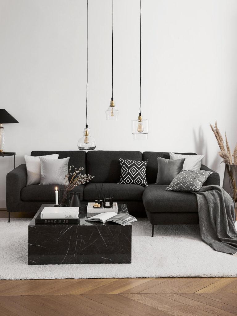 Salon gris avec canapé gris foncé, table basse en marbre et lampes suspendues