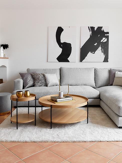 salon avec canapé gris, tables basses rondes en bois et peinture au mur