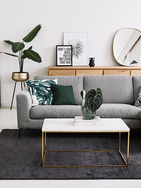 Salon tropical avec canapé gris, table effet marbre et coussins palmier