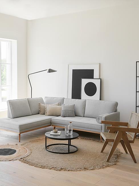 Salon gris avec canapé gris, fauteuil en cannage et cadres