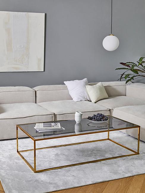 Salon avec canapé beige, mur gris clair et table basse en verre