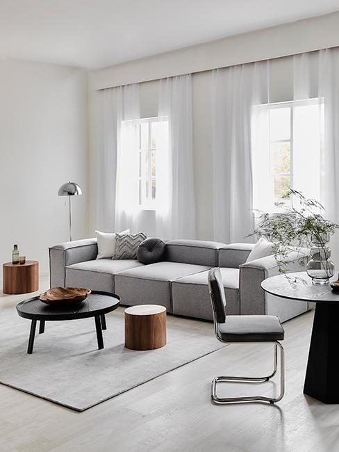 Salon avec canapé gris, tables basses et tapis gris