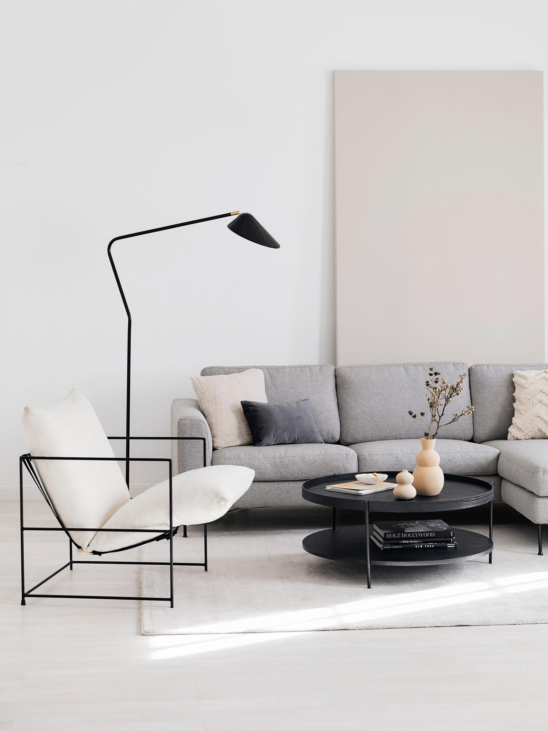 Salon avec canapé gris, fauteuil blanc, lampadaire noir et table basse ronde noire