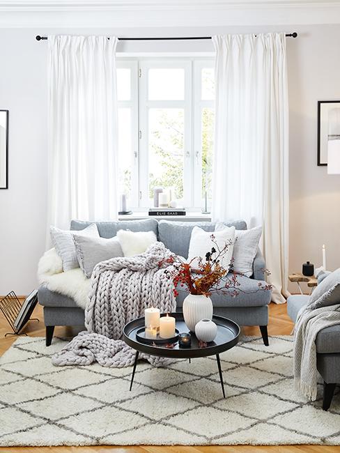 salon cosy avec canapé gris, plaid en laine, et tapis berbère