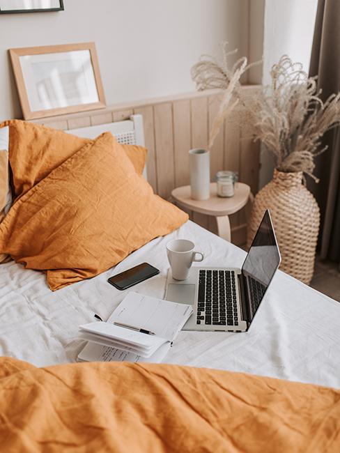 Chambre avec un ordinateur, un livre et un telephone sur un lit blanc et orange