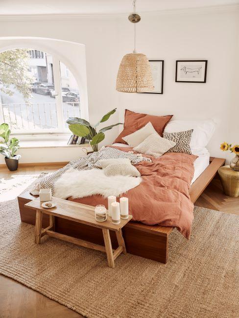 chambre à coucher boho, banc bout de lit en bois brut, tapis en jute, suspension en rotin