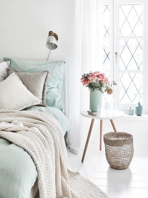chambre à coucher vert pastel, plaid, panier, bouquet de fleurs