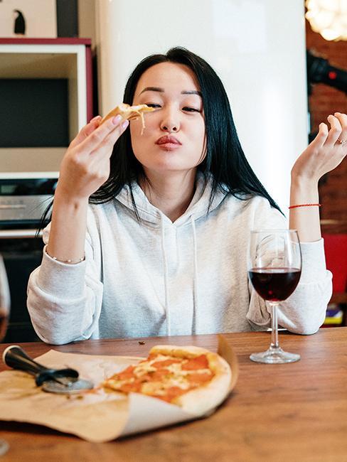 une jeune fille entrain de manger une part de pizza avec un verre de vin