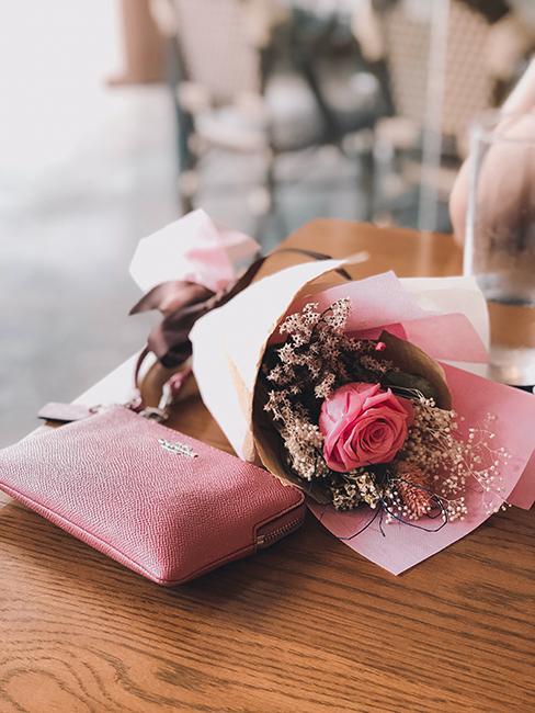 Un bouquet de roses avec un portemonnaie rose posés sur une table en bois