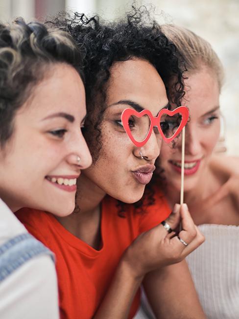 Trois filles entrain de se prendre en photo avec un accessoire de photobooth
