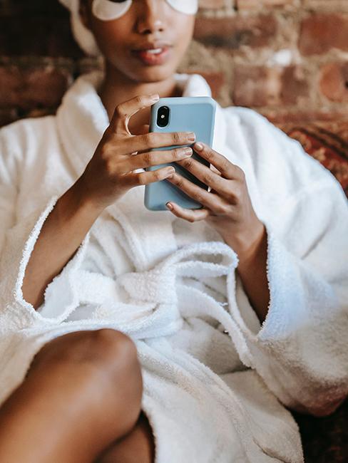 personne en peignoir blanc entrain de regarder son téléphone portable