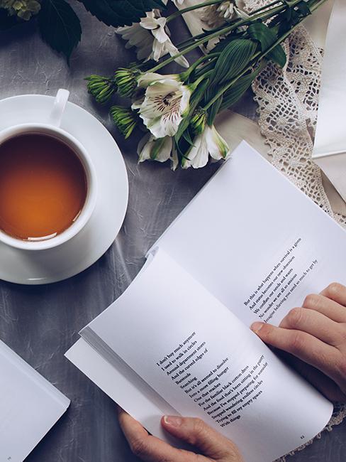 personne entrain de lire un livre avec une tasse de thé et des fleurs posées sur une table