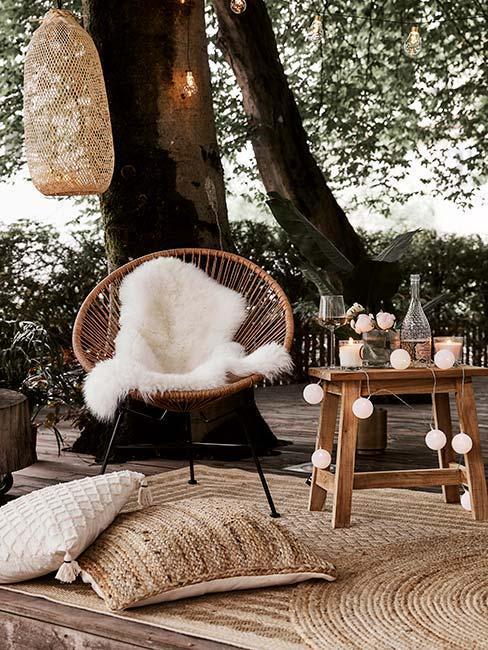 terrasse moderne naturelle avec chaise en fibres naturelles, plaid effet mouton, tapis de jute et tabouret en boi