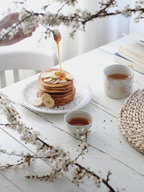 pancakes sur une asiette avec des bananes sur une table en bois blanc