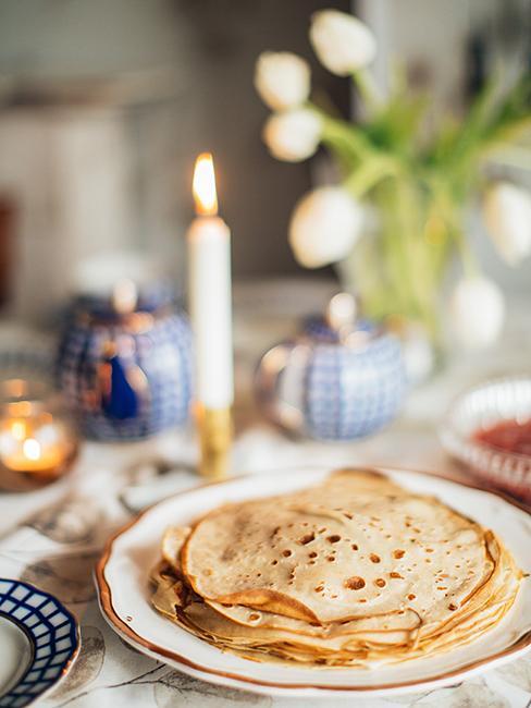 Crêpes dans une assiette posée sur une table avec une bougie