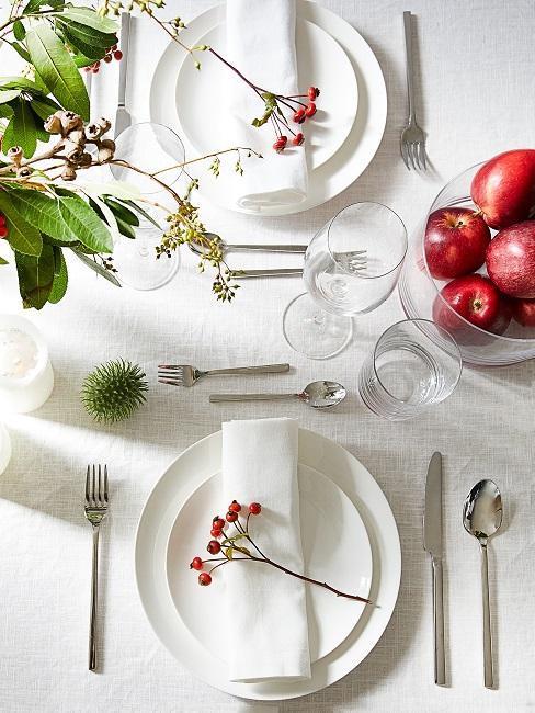 Table automnale avec vaisselle blanche, couverts argentés et fruits rouges