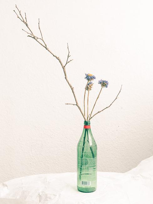 Décoration de table DIY avec une bouteille qui sert de vase avec des fleurs