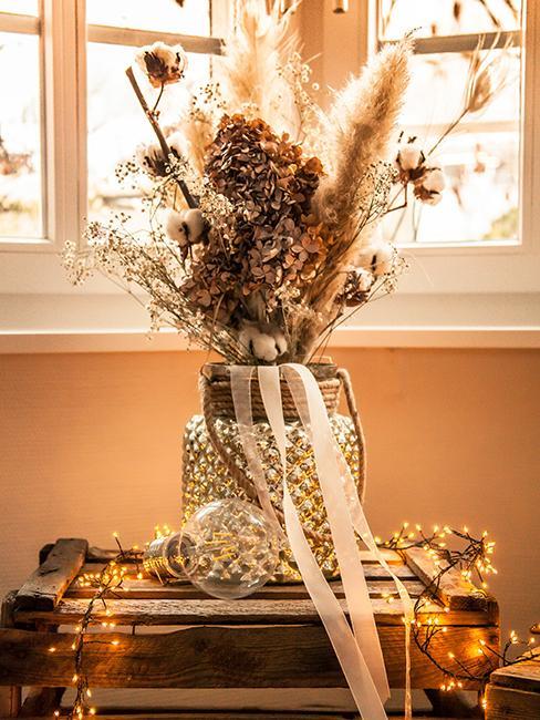 Vase en verre avec fleurs séchées et guirlande lumineuse