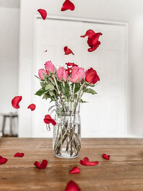 bouquet de roses dans un verre transparent sur une table en bois